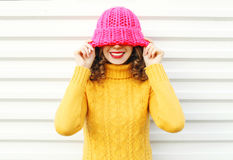 Fashion portrait happy young smiling woman wearing colorful pink knitted hat over white Stock Photos