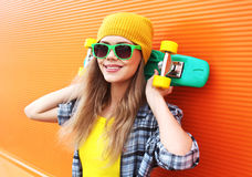 Fashion portrait of hipster cool girl in sunglasses with skate Royalty Free Stock Image