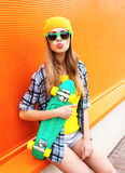 Fashion portrait of hipster cool girl in sunglasses with skateboard Royalty Free Stock Photography