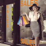 Fashion portrait of kitsch shopping girl in front of window shop Royalty Free Stock Photos