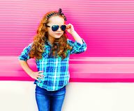 Fashion portrait little girl child in checkered shirt, sunglasses posing on colorful pink stock photos