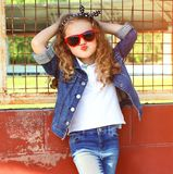 Fashion portrait little girl child in jeans jacket, red sunglasses posing stock images