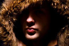 Fashion portrait of man in fur hood Stock Photos