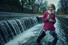 Fashion portrait of model in long pullover with dead fish in her hands standing in river of sewage against waterfall o Stock Photos