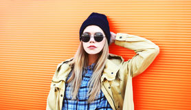 Fashion portrait pretty blonde woman in black sunglasses and hat on a colorful orange background Stock Image