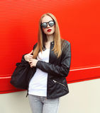 Fashion portrait pretty blonde woman wearing a rock black leather jacket, sunglasses and bag Stock Images