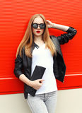 Fashion portrait pretty blonde woman wearing a rock black leather jacket, sunglasses and handbag clutch Stock Images