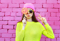 Fashion portrait pretty cool girl with lollipop having fun over colorful pink Royalty Free Stock Image