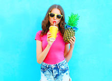Fashion portrait pretty cool girl and pineapple drinking juice from cup over colorful. Background royalty free stock images