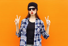 Fashion portrait pretty cool girl wearing a black hat, sunglasses and shirt. Over colorful background Stock Photo