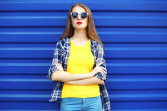 Fashion portrait of pretty girl in sunglasses. And colorful clothes over blue background royalty free stock image
