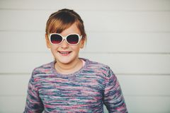 Fashion portrait of pretty little girl. Wearing sunglasses and purple pullover Royalty Free Stock Photography