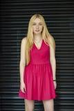 Fashion portrait of pretty young girl posing on dark wall b Stock Photos