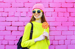 Fashion portrait pretty smiling girl with lollipop over colorful Stock Photography