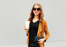 Fashion portrait pretty smiling woman with coffee cup and handbag clutch walking over grey. Background Stock Image