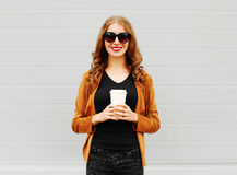 Fashion portrait pretty smiling woman holds coffee cup over grey. Background Stock Photo