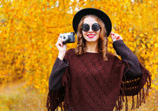 Fashion portrait pretty smiling woman with retro camera wearing autumn black hat sunglasses and knitted poncho over sunny yellow Stock Photography