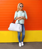 Fashion portrait of pretty smiling woman in sunglasses with bag. Against the colorful orange wall Royalty Free Stock Photos