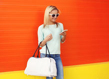 Fashion portrait of pretty smiling woman in sunglasses with bag. Using smartphone against the colorful orange wall Stock Photos