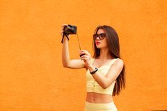 Fashion portrait of pretty smiling woman in sunglasses making photo by the camera against the grey wall. fitness stock images