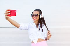 Fashion portrait of pretty smiling woman in sunglasses making selfie by the smartphone against the grey wall. Wireless Stock Photos