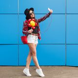 Fashion portrait of pretty smiling and woman in sunglasses with smartphone against the colorful blue wall. Make selfie. With balloon in her hand. Outdoor stock image