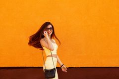 Fashion portrait of pretty smiling woman in sunglasses talking on the smartphone against the orange wall.fitness royalty free stock photos