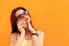 Fashion portrait of pretty smiling woman in sunglasses talking on the smartphone against the orange wall.fitness stock photo