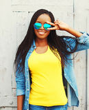 Fashion portrait pretty smiling young african woman in a sunglasses is having fun Royalty Free Stock Images