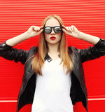 Fashion portrait pretty stylish woman with red lipstick wearing a rock black jacket and sunglasses. In city Stock Photos