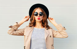 Fashion portrait pretty sweet young woman blowing red lips wearing a black hat sunglasses coat over grey stock photos