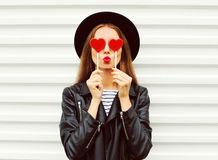 Fashion portrait pretty sweet young woman with red lips making air kiss with lollipop heart wearing black hat leather jacket. Over white background stock photography