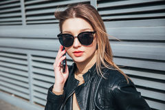 Fashion portrait pretty woman in black rock style in sunglasses using mobile phone over gray background in city Royalty Free Stock Photography