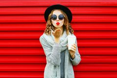 Fashion portrait pretty woman with coffee cup blows red lips. Sends an air kiss on a red background Royalty Free Stock Images