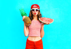 Fashion portrait pretty woman is holding a pineapple and a slice of watermelon Stock Image