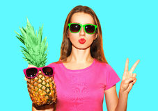 Fashion portrait pretty woman and pineapple with sunglasses. Over blue background Stock Images