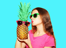 Fashion portrait pretty woman and pineapple in sunglasses. Over blue background Royalty Free Stock Image