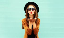 Fashion portrait pretty woman sends air sweet kiss in black round hat stock images