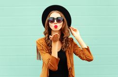 Fashion portrait pretty woman sends air sweet kiss in black round hat stock photography
