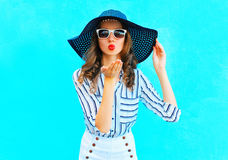 Fashion portrait pretty woman in straw summer hat is sends an air kiss over colorful blue Royalty Free Stock Photo