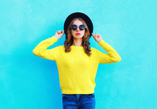 Fashion portrait pretty woman wearing a black hat and yellow knitted sweater over colorful blue. Background Royalty Free Stock Images