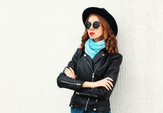 Fashion portrait pretty woman wearing black rock jacket, hat over white background Royalty Free Stock Image