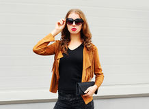 Fashion portrait pretty woman wearing a sunglasses, brown jacket and black handbag over grey Royalty Free Stock Image