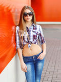 Fashion portrait pretty woman wearing a sunglasses and checkered shirt Stock Images