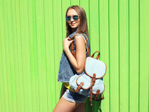 Fashion portrait of pretty woman wearing a sunglasses and jeans. Clothes with backpack over colorful green wall Stock Images