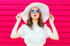Fashion portrait pretty woman in white summer straw hat over colorful pink Stock Image