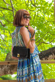 Fashion portrait of pretty young caucasian woman with handmade snakeskin python handbag. Sunny day on a tropical Bali Royalty Free Stock Image