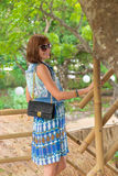Fashion portrait of pretty young caucasian woman with handmade snakeskin python handbag. Sunny day on a tropical Bali Stock Photos