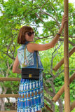 Fashion portrait of pretty young caucasian woman with handmade snakeskin python handbag. Sunny day on a tropical Bali Royalty Free Stock Images