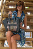 Fashion portrait of pretty young caucasian woman with handmade snakeskin python handbag. Sunny day on a tropical Bali Stock Photo